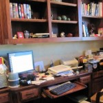 Messy, cluttered desk and bookcase